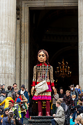 © Licensed to London News Pictures. 23/10/2021. LONDON, UK.  Little Amal, a 3.5m tall living artwork, stands outside St Paul's Cathedral.  She is taking part in The Walk, produced by Good Chance Theatre, travelling 8,000km in support of refugees. Created by Handspring Puppet Company, Little Amal represents a young Syrian refugee child who walked from Turkey across Europe to the UK and her journey will end in Manchester in November.  Photo credit: Stephen Chung/LNP