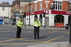 © Licensed to London News Pictures. 28/05/2021. London, UK. Police officers guard a crime scene outside Costa Coffee on High Road, Wood Green, north London, following a death of a man. Police were called at just after 1am on Friday, 28 May to reports of a firearm discharge in the vicinity of Turnpike Lane. Police officers, the London Ambulance Service and London's Air Ambulance attended the scene. A man, believed to be aged in his 20s, was found suffering a gunshot injury. Despite the efforts of the emergency services he was pronounced dead at the scene at just before 2am. Photo credit: Dinendra Haria/LNP