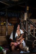 Port Barton, Palawan, Philippines - July 8, 2019:  Shellem nurses her daughter Xena at the open-air restaurant at Deep Moon Resort in Port Barton.