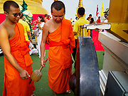 15 NOVEMBER 2018 - BANGKOK, THAILAND: Monks bang a prayer gong during the red cloth ceremony at Wat Saket, also called the Golden Mount. Wat Saket is on a man-made hill in the historic section of Bangkok. The temple has golden spire that is 260 feet high, which was the highest point in Bangkok for more than 100 years. The temple construction began in the 1800s during the reign of King Rama III and was completed in the reign of King Rama IV. A  red cloth (reminiscent of a monk's robe) is placed around the chedi at the top of  Golden Mount during the weeks leading up to the Thai holy day of Loy Krathong, which is November 22 this year.       PHOTO BY JACK KURTZ
