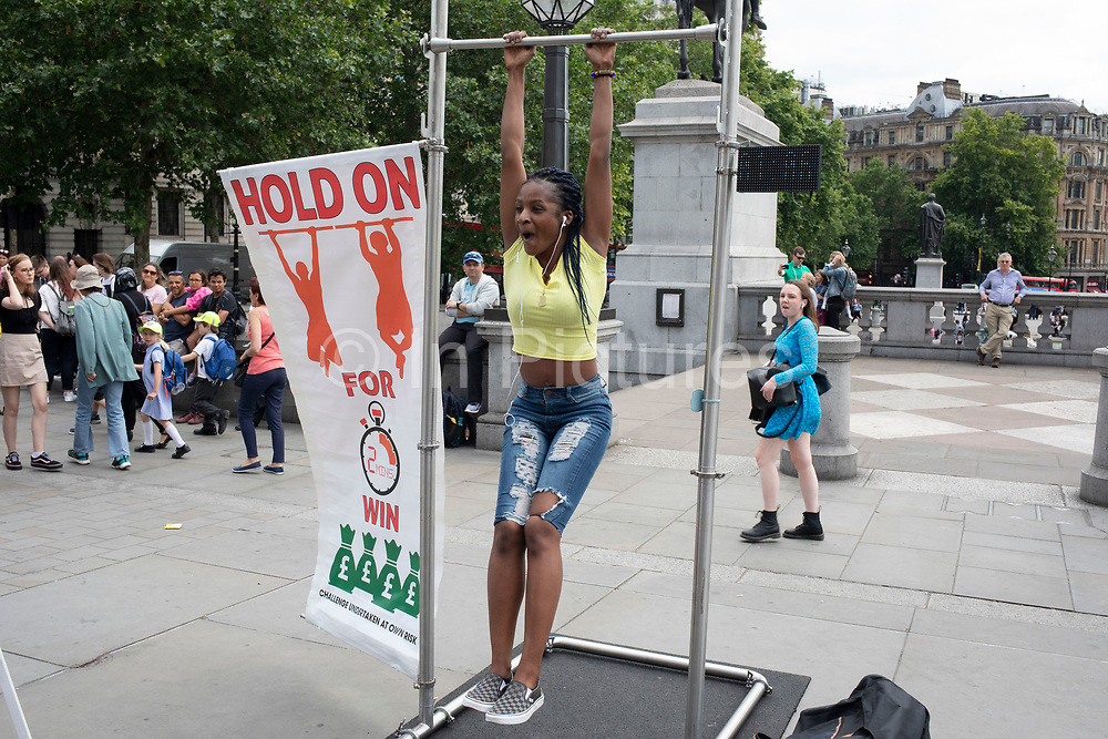 Contestants in Trafalgar Square attempt to hang on to a horizontal bar in an attempt to win one hundred pounds in London, United Kingdom. Each contestant pays ten pounds and tries to hang on for one and a half minutes for women and two minutes for men. Some passers by comment that this is a scam, but hanging on is possible, if difficult.