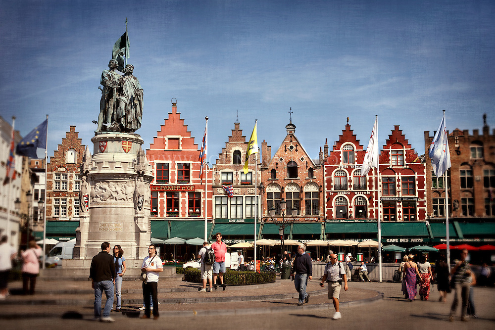 Facades of colorful buildings and people enjoying the Markt in Bruges, Belgium.