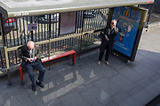 An elderly gentleman wipes his spectacles clean with a cloth, as a lady raises hers to see oncoming buses, on Denmark Hill in Southwark, on 28th March 2019, in London, England