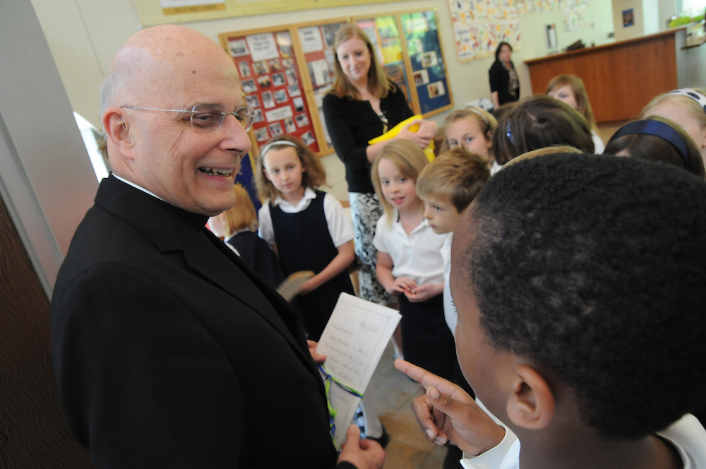 Archbishop Francis Cardinal George greets students at Old St. Mary's Catholic School after a ground breaking ceremony for the institution's expansion.