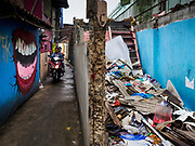 """22 MARCH 2018 - BANGKOK, THAILAND:  A motorcycle goes past a demolished home along Khlong Lat Phrao. Bangkok officials are evicting about 1,000 families who have set up homes along Khlong  Lat Phrao in Bangkok, the city says they are """"encroaching"""" on the khlong. Although some of the families have been living along the khlong (Thai for """"canal"""") for generations, they don't have title to the property, and the city considers them squatters. The city says the residents are being evicted so the city can build new embankments to control flooding. Most of the residents have agreed to leave, but negotiations over compensation are continuing for residents who can't afford to move.     PHOTO BY JACK KURTZ"""