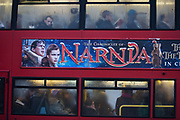 London bus passengers endure the misery of another morning commute into the city. As they sit looking miserable, squashed in the bus, its windows steamed up they are unaware of The Chronicles of Narnia movie poster that shows itself to the outsider. In the panoramic banner often used by the film industry for forthcoming movie productions, we see the main characters from Narnia in heroic, romantic and epic story roles. But the reality of another commute into London is also a heroic experience when wintry conditions often stop the flow of public transport and its infrastructure. The Chronicles of Narnia is a series of seven fantasy novels for children written by C. S. Lewis. It is considered a classic of children's literature and is the author's best known work, having sold over 100 million copies in 47 languages.