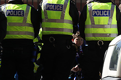 A young boy tries to get a glimpse of the teams arriving between police officers legs at the Ladbrokes Scottish Premiership match at Ibrox Stadium, Glasgow.