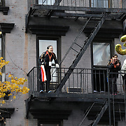 Spectators watch from vantage points as runners make their way along First Avenue in Manhattan, New York, during the ING New York Marathon. New York, USA. 3rd November 2013. Photo Tim Clayton