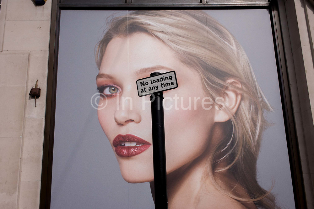 A No Loading parking sign obscures the right eye of a female model outside a fashion retailer in Oxford Street, central London. Carefully juxtaposed against the poster, we see the tall sign obscuring one of the woman's eyes - as if an eye patch.