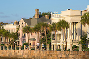 People walk along the battery seawall past stately antebellum historic homes in Charleston, SC.