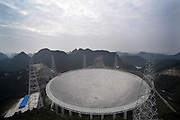 """QIANNAN, CHINA - SEPTEMBER 17: <br /> <br /> Aerial view of a dish-like radio telescope at Pingtang County on September 17, 2016 in Qiannan Buyei and Miao Autonomous Prefecture, Guizhou Province of China. After five years construction, \""""Five hundred meter Aperture Spherical Telescope (FAST) will be put into use on September 25. The local public security bureau has intensified security since September 16 in the core zone and around the radio telescope to ensure the radio telescope\'s completion goes well. <br /> ©Exclusivepix Media"""