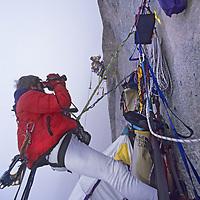 BAFFIN ISLAND, Canada. John Catto films Greg Child (MR) high up 4000' granite face on Great Sail Peak.