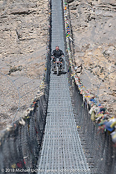 Scotty Busch riding across a narrow suspension bridge over the Kali Gandaki River on day-6 of our Himalayan Heroes adventure riding from Muktinath to Tatopani, Nepal. Sunday, November 11, 2018. Photography ©2018 Michael Lichter.