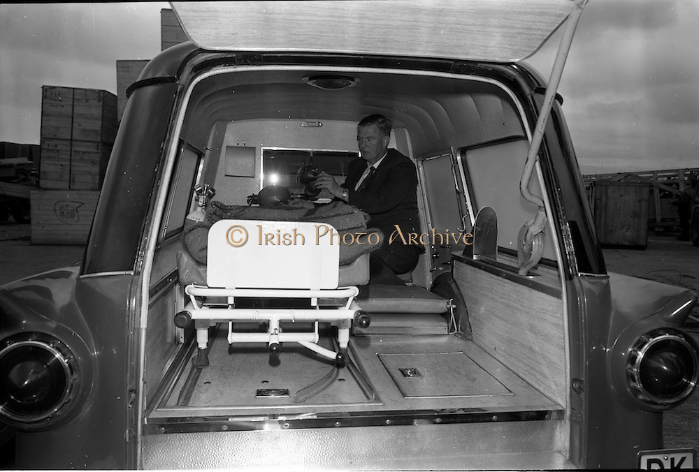 """25/06/1963<br /> 06/25/1963<br /> 25 June 1963<br /> Ford station wagon Ambulance being unloaded from the ship the """"City of Cork"""" at the North Wall, Dublin port. View of the interior of the ambulance."""