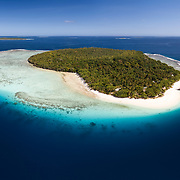 Aerial panorama of Eueiki Island in the Vava'u island group of the Kingdom of Tonga. Located on the island is Treasure Island Resort, visible in this photo. There is a large school of sardines near the boats.