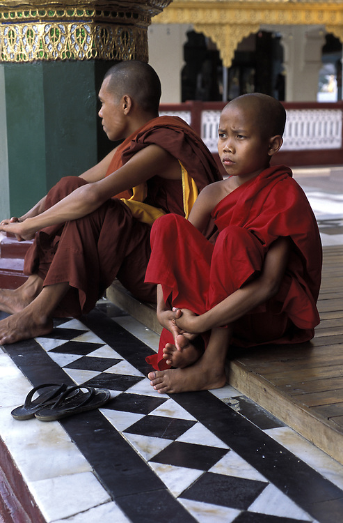 A Buddhist monk and his student visit Shwedagon, in Yangon.<br /> <br /> Monks congregate in one of the many surrounding temples of Shwedagon.<br /> <br /> Shwedagon Zedi Daw The, as it is known locally,or The Crown of Burma less formally, is rumoured to be the oldest pagoda in the world dating to 2,600 years old. Standing 99m tall and crowning a hilltop, it can be seen from all over Yangon, by day and night.<br /> <br /> The main gold-plated dome is topped by a stupa containing over 7,000 diamonds, rubies, topaz' and sapphires,all offset by a massive emerald positioned to reflect the setting sun.<br /> <br /> As Myanmar's most revered shrine it has always been customary for families and followers of the Buddha to make the pilgrimage to Shwedagon in the same way that Muslims feel compelled to visit the Kaaba at Mecca, at least once in their lifetime.