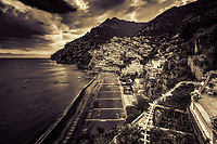 """""""Ominous evening clouds above Positano - BW""""…<br /> <br /> After an exhilarating drive along the high cliffs on the Amalfi coast from Sorrento down to Positano, I found myself in sensory overload with its beauty and photogenic appeal.  After circling around the entire village and its cliffside three times on Positano's only street, which was a single lane winding down from the top and back up and over to where I began, I finally found the parking garage by the hotel, about 2/3rds up the facing village in this image.  The climb down the winding road and steep staircases made for quite a workout in the hot late May sun.  Reaching the beach and marina, I forgot about my exhaustion and could not capture enough of Positano's plush beauty; however, the large amount of tourists and bright sun did not allow for ideal conditions.  Walking the length of the beach, I found a very, very steep staircase leading straight up to a large veranda at the Albergo California.  Taking an exhaustive seat on a plush lounge chair with a perfect view to watch the sunset behind the Amalfi Cliffs, I was taken back by a pleasant Italian (Positano) waiter from the hotel offering a towel, ice water, and drinks for the evening.  I expressed that I was not staying at the hotel, but he didn't seem to mind and proceeded to educate me on the culture of this historic resort village.  The sunset was being coy and didn't appear to cooperate, but during opportune moments it mystified the ominous clouds, and contributed just enough light and color to satisfy a weary photographer."""