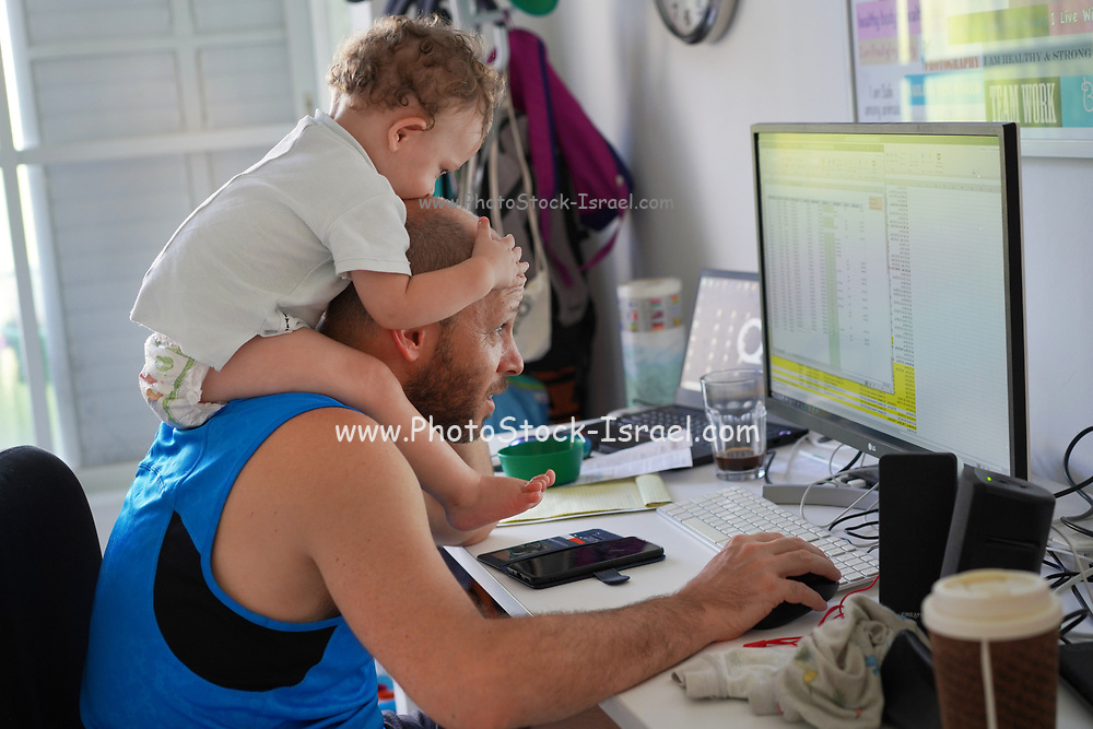 Young playful toddler boy at work with his father while sitting on his fathers shoulders