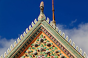 "09 MARCH 2009 -- BANGKOK, THAILAND: Architectural detail of Wat Arun. Wat Arun is a Buddhist temple (wat) in the Bangkok Yai district of Bangkok, Thailand, on the west bank of the Chao Phraya River. The full name of the temple is Wat Arunratchawararam Ratchaworamahavihara. The outstanding feature of Wat Arun is its central prang (Khmer-style tower). It may be named ""Temple of the Dawn"" because the first light of morning reflects off the surface of the temple with a pearly iridescence. Steep steps lead to the two terraces. The height is reported by different sources as between 66,80 m and 86 m. The corners are surrounded by 4 smaller satellite prangs. The prangs are decorated by seashells and bits of porcelain which had previously been used as ballast by boats coming to Bangkok from China. The central prang is topped with a seven-pronged trident, referred to by many sources as the ""trident of Shiva"". Around the base of the prangs are various figures of ancient Chinese soldiers and animals. Over the second terrace are four statues of the Hindu god Indra riding on Erawan. The temple was built in the days of Thailand's ancient capital of Ayutthaya and originally known as Wat Makok (The Olive Temple). In the ensuing era when Thonburi was capital, King Taksin changed the name to Wat Chaeng. The later King Rama II. changed the name to Wat Arunratchatharam. He restored the temple and enlarged the central prang. The work was finished by King Rama III. King Rama IV gave the temple the present name Wat Arunratchawararam. As a sign of changing times, Wat Arun officially ordained its first westerner, an American, in 2005. The central prang symbolizes Mount Meru of the Indian cosmology. The satellite prangs are devoted to the wind god Phra Phai.  Photo by Jack Kurtz"