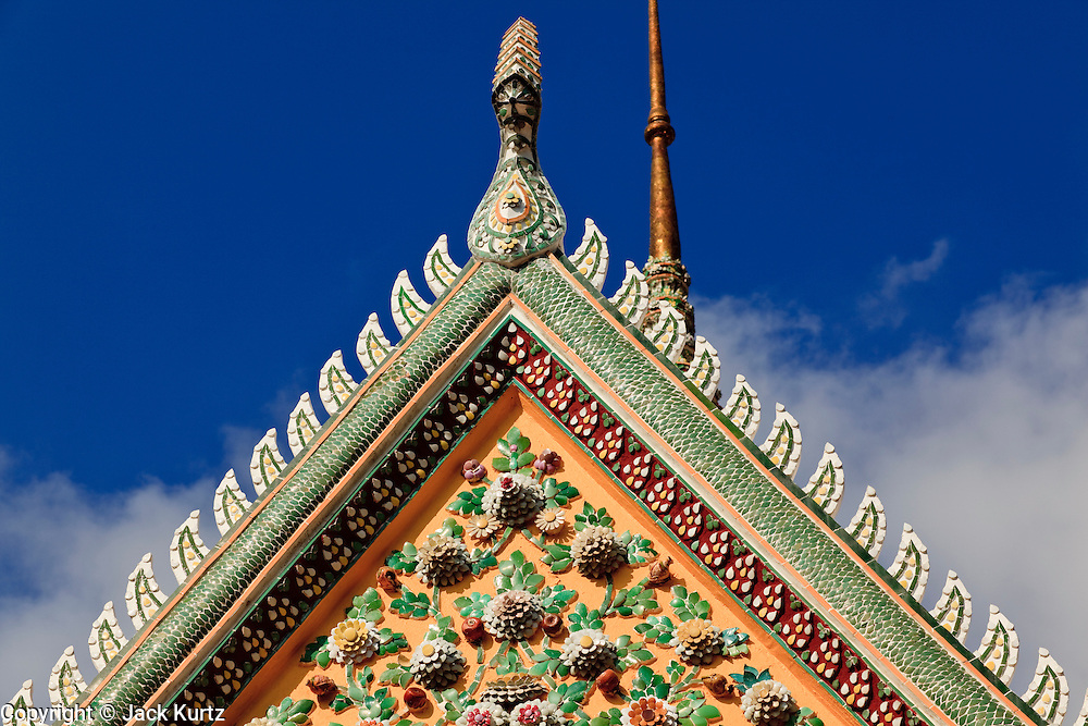 """09 MARCH 2009 -- BANGKOK, THAILAND: Architectural detail of Wat Arun. Wat Arun is a Buddhist temple (wat) in the Bangkok Yai district of Bangkok, Thailand, on the west bank of the Chao Phraya River. The full name of the temple is Wat Arunratchawararam Ratchaworamahavihara. The outstanding feature of Wat Arun is its central prang (Khmer-style tower). It may be named """"Temple of the Dawn"""" because the first light of morning reflects off the surface of the temple with a pearly iridescence. Steep steps lead to the two terraces. The height is reported by different sources as between 66,80 m and 86 m. The corners are surrounded by 4 smaller satellite prangs. The prangs are decorated by seashells and bits of porcelain which had previously been used as ballast by boats coming to Bangkok from China. The central prang is topped with a seven-pronged trident, referred to by many sources as the """"trident of Shiva"""". Around the base of the prangs are various figures of ancient Chinese soldiers and animals. Over the second terrace are four statues of the Hindu god Indra riding on Erawan. The temple was built in the days of Thailand's ancient capital of Ayutthaya and originally known as Wat Makok (The Olive Temple). In the ensuing era when Thonburi was capital, King Taksin changed the name to Wat Chaeng. The later King Rama II. changed the name to Wat Arunratchatharam. He restored the temple and enlarged the central prang. The work was finished by King Rama III. King Rama IV gave the temple the present name Wat Arunratchawararam. As a sign of changing times, Wat Arun officially ordained its first westerner, an American, in 2005. The central prang symbolizes Mount Meru of the Indian cosmology. The satellite prangs are devoted to the wind god Phra Phai.  Photo by Jack Kurtz"""