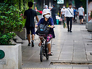 31 JANUARY 2019 - BANGKOK, THAILAND:   A woman wearing a breathing mask rides her bike down a Bangkok sidewalk. The Thai government has closed more than 400 schools for the rest of the week because of high levels of pollution in Bangkok. At one point Wednesday, Bangkok had the third highest level of air pollution in the world, only Delhi, India and Lahore, Pakistan were worst. The Thai government has suspended some government construction projects and ordered other projects to take dust abatement measures. Bangkok authorities have also sprayed water into the air in especially polluted intersections to control dust. Bangkok's AQI (Air Quality Index) Thursday morning was 180, which is considered unhealthy for all people.   PHOTO BY JACK KURTZ