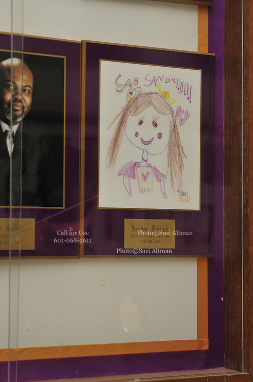 """Pictured is a crayon portrait of Actress Sandra Bullock in a display case, where a photo should be, at the Warren Easton Charter high school in New Orleans Louisiana. The display case hold photographs of individuals who have helped the school and are """"honorary friends"""" of the school. Bullock was at the school Aug. 29,2010 on the 5th year anniversary of Hurricane Katrina to cut a ribbon at the opening of the health clinic. Photo©Suzi Altman"""