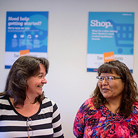Member Services and Outreach Director Debbie Rochford, left, and enrollment counselor Carol Edison laugh and talk during an open house for health insurance exchange BeWellNM Wednesday in Gallup.