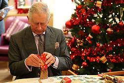 December 22, 2016 - Cheltenham, United Kingdom - Image icensed to i-Images Picture Agency. 22/12/2016. Cheltenham, United Kingdom. The Prince of Wales looks inside a Christmas cracker  during a visit to the Sue Ryder Leckhampton Court Hospice in  Cheltenham , United Kingdom. Picture by ROTA / i-Images  UK OUT FOR 28 DAYS (Credit Image: © Rota/i-Images via ZUMA Wire)