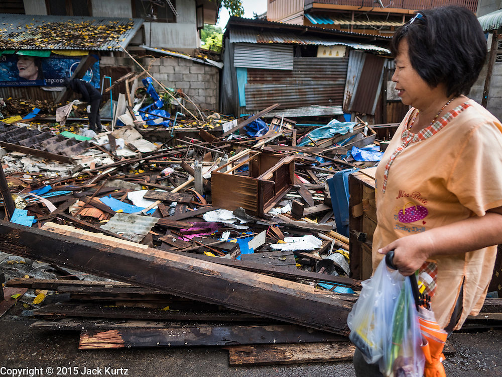 28 SEPTEMBER 2015 - BANGKOK, THAILAND:  A woman who lives in the Wat Kalayanamit neighborhood walks past a destroyed home. Fifty-four homes around Wat Kalayanamit, a historic Buddhist temple on the Chao Phraya River in the Thonburi section of Bangkok, are being razed and the residents evicted to make way for new development at the temple. The abbot of the temple said he was evicting the residents, who have lived on the temple grounds for generations, because their homes are unsafe and because he wants to improve the temple grounds. The evictions are a part of a Bangkok trend, especially along the Chao Phraya River and BTS light rail lines. Low income people are being evicted from their long time homes to make way for urban renewal.   PHOTO BY JACK KURTZ