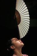 BEIJING, CHINA - 9 DECEMBER 2005 - A woman balances a paper fan on the tip of her nose during a practise session in Beijing's Chaoyang Theatre December 9, 2005. Records of acrobatic acts can be found as early as the Ch'in Dynasty (221 B.C. - 207 B.C.) and Chinese acrobats through the ages have continued to perfect what has become an evolving folk art form. Photo by Natalie Behring
