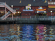 Neon signs of Carousel and the Fishermans restaurants reflect in Puget Sound waters, seen from downtown piers, Seattle, Washington, USA.