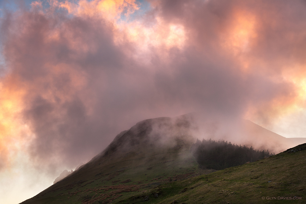 Low cloud rolling in from the Irish Sea wraps around the summit of Mynydd Mawr and adjacent peaks of the Welsh mountains of Snowdonia at sunset. The top of a pine woodland can be seen on the hillside, separated from the background by  sheets of hill fog.