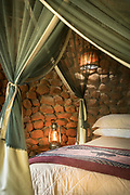 View of bedroom at Stone Camp containing bed and lamps, Mkhaya Game Reserve, Eswatini