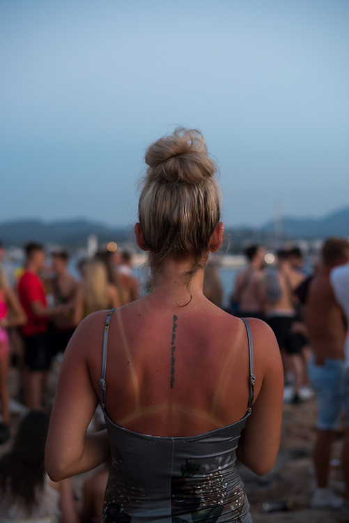Laura from England, visiting Ibiza for several days, in a crowd just after sunset in Sant Antoni. (August 2018)