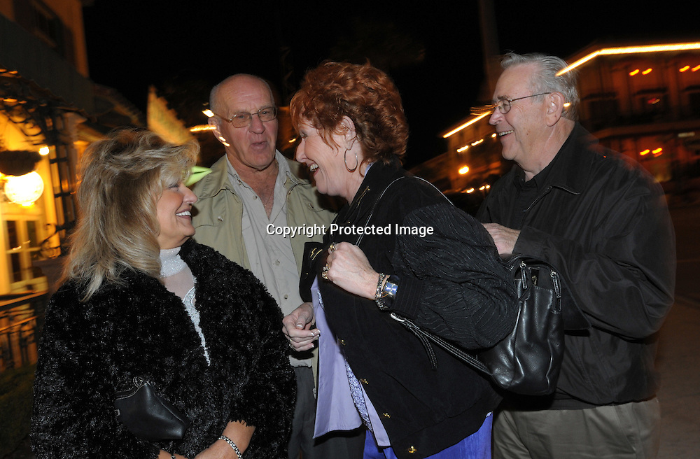 Friends Carol Ferrarelli, 60, from left, Jim Allingham, 70, Marilyn Whitley, 62, and Ed Whitley hop between bars in the main downtown square of The Villages, Fla., Saturday, Jan. 17, 2009. (Photo by Phelan M. Ebenhack)