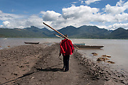 Boatman walks towards his boat with oars at a lake in the shadow of mountains in Lashihai near to Lijiang, Yunnan province, China. This is a predominantly Naxi minority area.