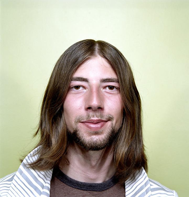 Young man with long hair and beard smiling at camera.