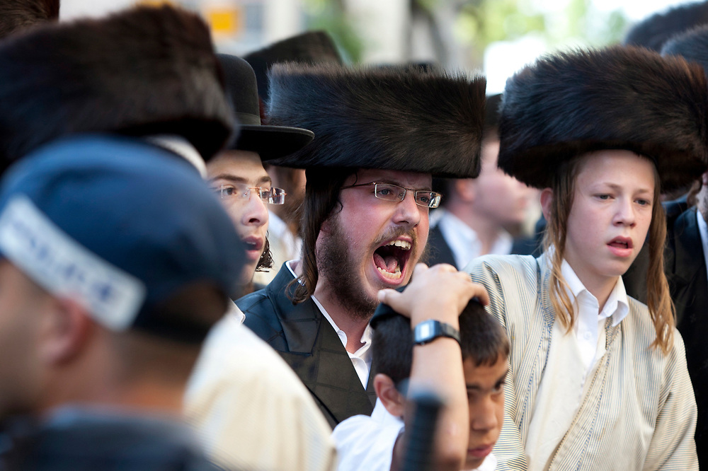 Ultra-Orthodox protesters shout at policemen as they attempt to block Neviim Street, a central thoroughfare in Jerusalem on July 16, 2011. Close to a thousand ultra-Orthodox Jewish men held a demonstration against the desecration of Shabbat, marking one hundred weekends to the opening of the Karta municipal parking lot in the capital.