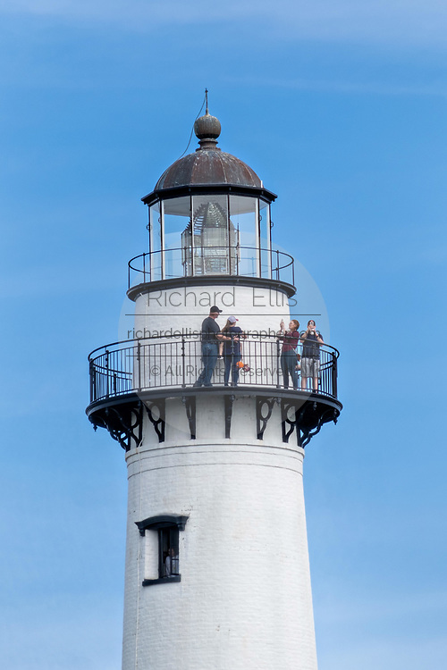 Tourists take selfies on the catwalk of the St. Simons Lighthouse at Coupers Point along the Saint Simons Sound in St. Simons Island, Georgia. The working lighthouse was built in first constructed in 1807 but destroyed by Confederate forces in 1862 before being rebuilt in 1872.