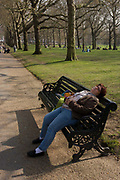 Still holding tight on to a pamphlet for the David Hockney art show, a foreign tourist has fallen asleep on a public bench in Green Park. The day of touring Britain's capital has proved too much for this visitor who has instinctively fallen unconscious on the curved lines of the bench a few metres from Piccadilly. In the distance we see the tall London Plane trees that line the path towards Buckingham Palace.