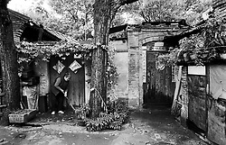 Woman sweeping steps of her old house in a soon to be demolished district of Beijing China