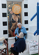 Shop keepers sit and talk in front of the stores on the island of Mykonos, Greece.  Photograph by Dennis Brack
