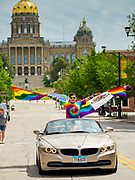 """28 JUNE 2020 - DES MOINES, IOWA:  A woman with American and Mexican versions of the Pride Flag participates in the Capitol City Pride Parade in Des Moines. The State Capitol is in the background. Most of the Pride Month events in Des Moines were cancelled this year because of the COVID-19 pandemic, but members of the Des Moines LGBTQI community, and Capitol City Pride, the organization that coordinates Pride Month events, organized a community """"parade"""" of people driving through the East Village of Des Moines displaying gay pride banners and flags. About 75 cars participated in the parade.     PHOTO BY JACK KURTZ"""