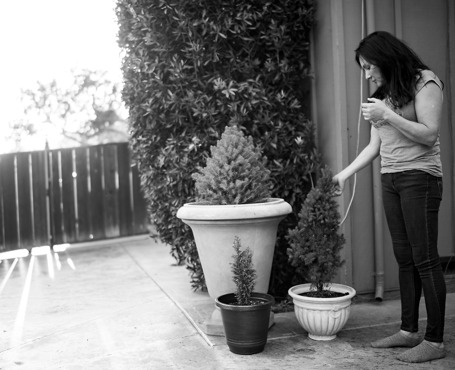 """Veronica Ramirez looks at new growth on a 2-foot pine tree in a large pot at her home on March 28, 2018. Her late-son's ashes were planted underneath three saplings.<br /> <br /> """"I am compelled to give my son life again and watch him grow,"""" she said in 2016 when she first planted the trees. """"I pray somehow all his heart and soul spread throughout this Earth."""""""
