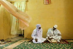 Sidi Alimam, 32, is working wth Abdl Haidara to restore thousands of manuscripts at the newly built Al Moustapha Konate de Maigala library library of Timbuktu, Mali March 11, 2007. Here he is shown reading an ancient manuscripts with his uncle Alphady Ascopfare, (left) and another relative Mohammed Maiga (wearing brown) in their home. In the past few years, with funding from different organizations including the Ford Foundation, thousands of the manscripts are being recovered, stored, preserved and studied. Sadly, many of them have been lost or severley damaged but for those that remain it is a maginifcent reminder of Africa's literary history.  (Photo by Ami Vitale)