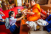 10 APRIL 2013 - CHIANG MAI, CHIANG MAI, THAILAND:  A monk ties a string bracelet on a schoolgirl's wrist after she made a Songkran offering at Wat Phra Singh in Chiang Mai. Songkran is celebrated in Thailand as the traditional New Year's Day from 13 to 16 April. Songkran is in the hottest time of the year in Thailand, at the end of the dry season and provides an excuse for people to cool off in friendly water fights that take place throughout the country. The traditional Thai New Year has been a national holiday since 1940, when Thailand moved the first day of the year to January 1. The first day of the holiday period is generally the most devout and many people go to temples to make merit and offer prayers for the new year.    PHOTO BY JACK KURTZ