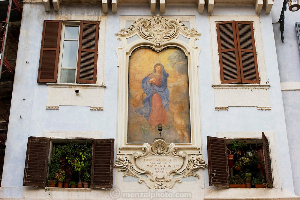 Building detail of shuttered windows and painting of the virgin in the Piazza Navonna, Rome, Italy.