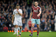 Angel Rangel of Swansea City (l) and Kevin Nolan, the West Ham United Captain ® look on. Barclays Premier league match, West Ham Utd v Swansea city at the Boleyn ground, Upton Park in London on Sunday 7th December 2014.<br /> pic by John Patrick Fletcher, Andrew Orchard sports photography.