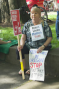 A woman protester at a 2015 Portland, Oregon May Day rally takes a rest while holding three different protest signs whose messages say Black LIves Matter Too, Oregon Needs Change, and Stop FastTrack and TPP.