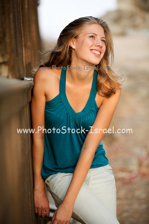 Young blonde woman in green top photographed outdoors